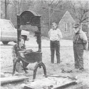 Walter Clement (kneeling) examines the Washington press on the lawn of the Elk Valley Times before loading. Complete restoration of the press will take several months (years).